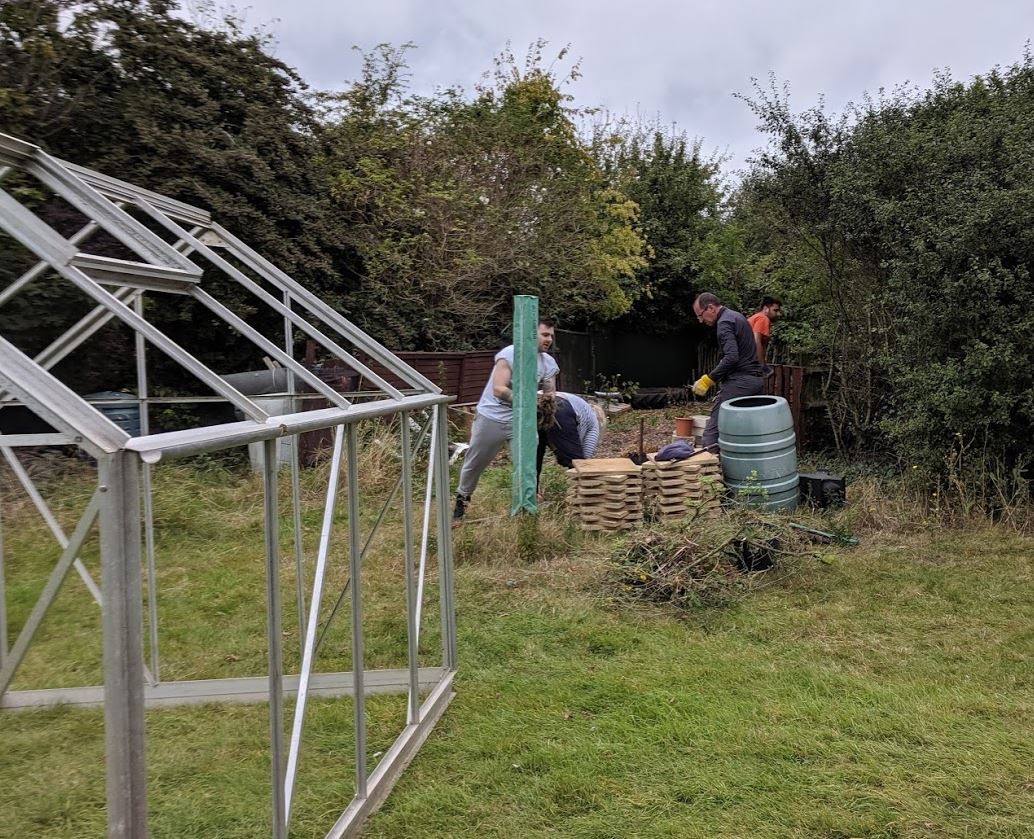 The Allianz UK volunteers started clearing the area for the greenhouse